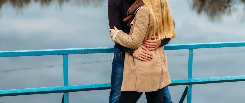 Par som omfamnar på bron, nära vattnet, höst förälskelse och familjen, ett datum i parkerar vid floden royaltyfria foton