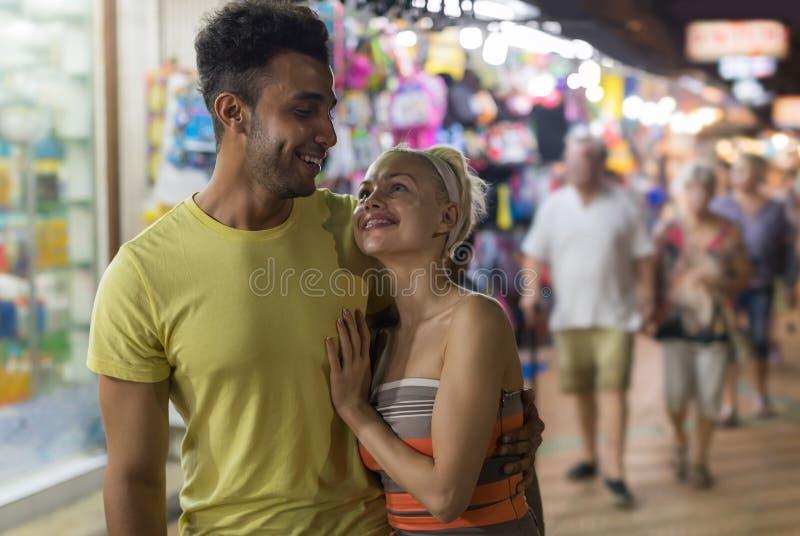 Par som omfamnar på gatamarknad, blandningloppman och lyckligt le för kvinna se de royaltyfria foton