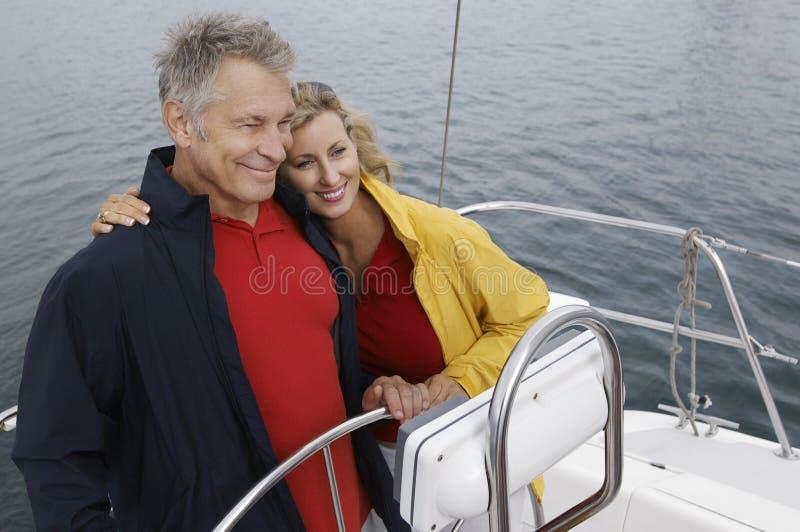 Par som omfamnar på segelbåten arkivbilder