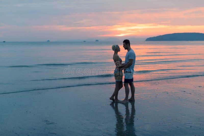 Par som omfamnar på stranden på solnedgången, den unga turist- mannen och kvinnakramen på sjösidan royaltyfri bild