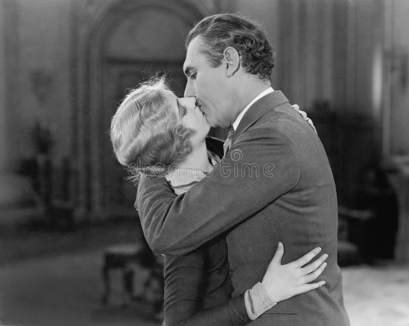 Par som omfamnas och kyssas (alla visade personer inte är längre uppehälle, och inget gods finns Leverantörgarantier det royaltyfria foton