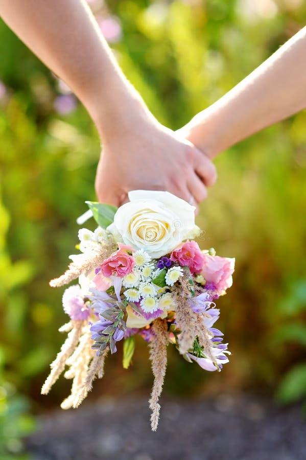 Par som rymmer buketten för lösa blommor arkivfoto