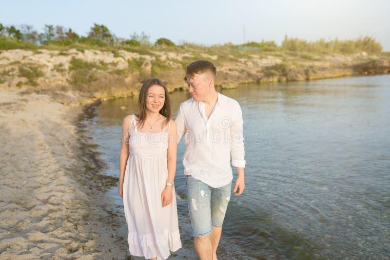 Par som rymmer händer som går romantiker på stranden på semesterloppferier royaltyfri fotografi