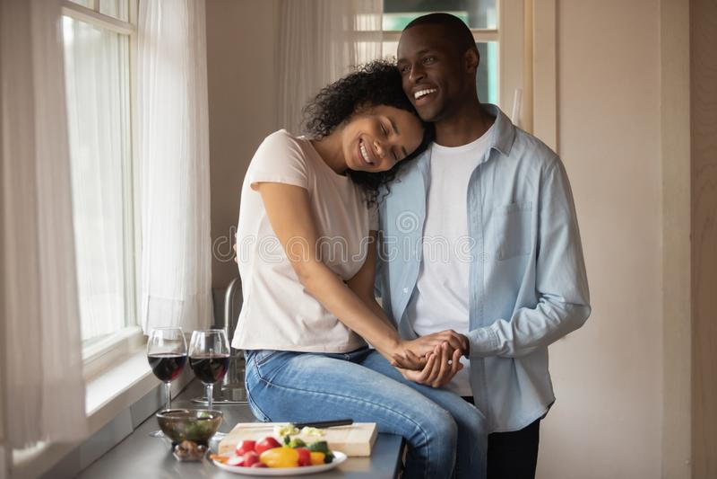 Par som rymmer händer som känner sig för att älska för att tycka om datumet i köket royaltyfri fotografi