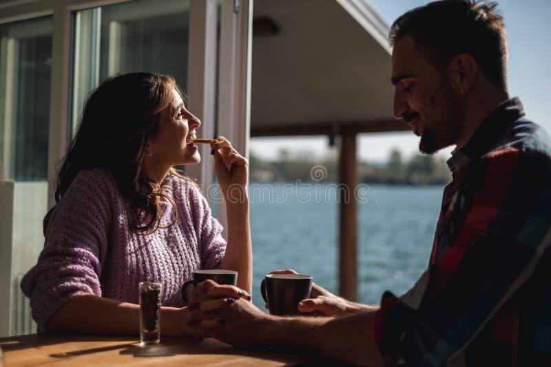 Par som rymmer händer, medan flickan äter kakan royaltyfri fotografi