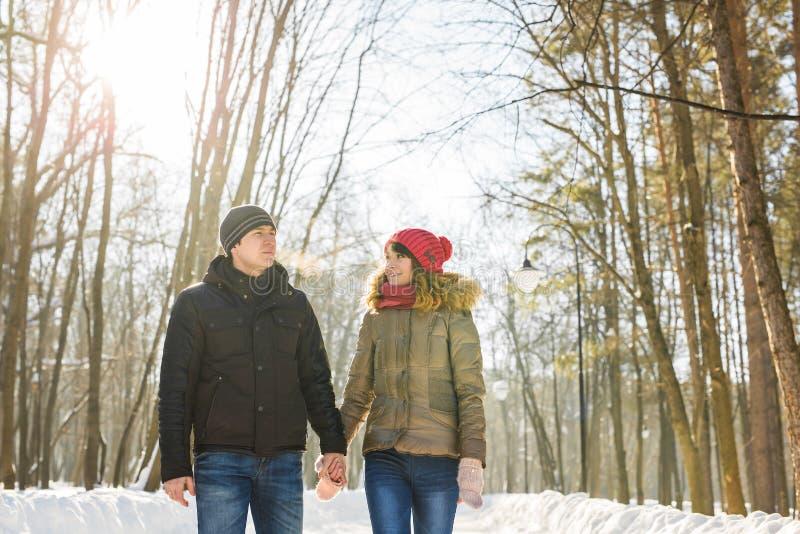 Par som rymmer sig & x27; s-händer, vintern går på vägen som tycker om en promenad, ett förälskelsepar Maken och frun är royaltyfri foto
