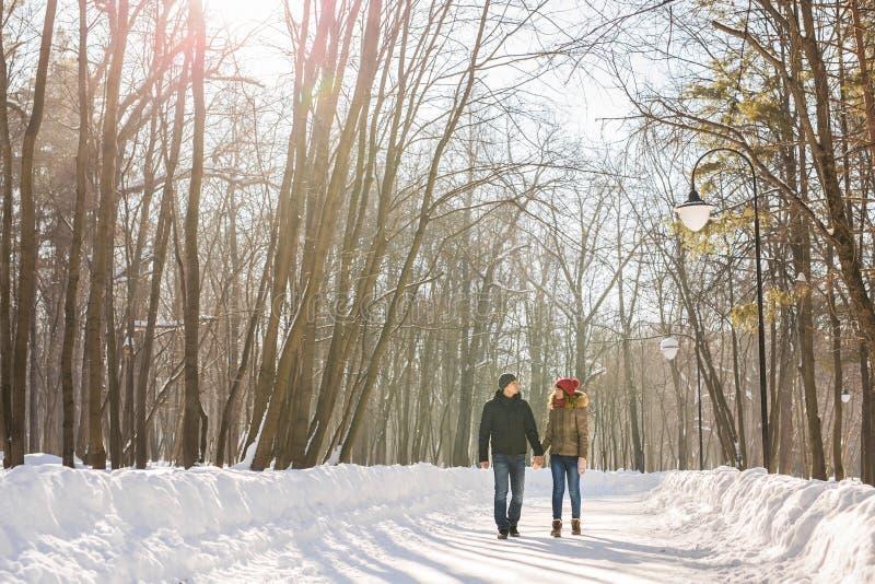 Par som rymmer sig & x27; s-händer, vintern går på vägen som tycker om en promenad, ett förälskelsepar Maken och frun är arkivfoton