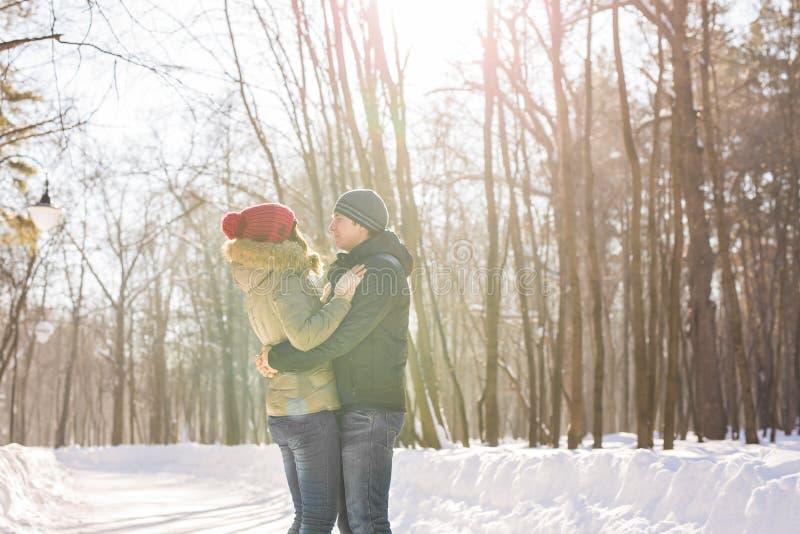 Par som rymmer sig & x27; s-händer, vintern går på vägen som tycker om en promenad, ett förälskelsepar Maken och frun är royaltyfri bild