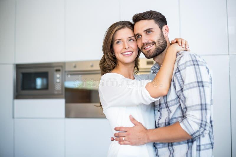 Par som ser bort, medan omfamna i kök arkivfoto