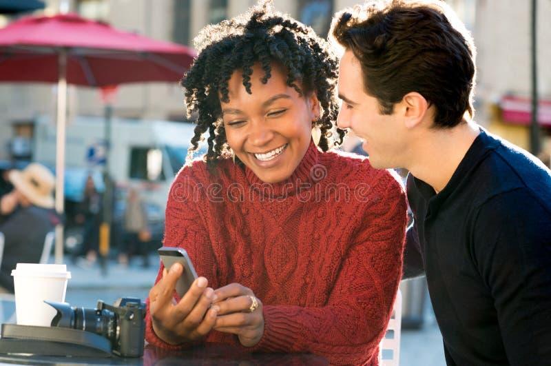 Par som ser den utomhus- telefonen royaltyfri bild