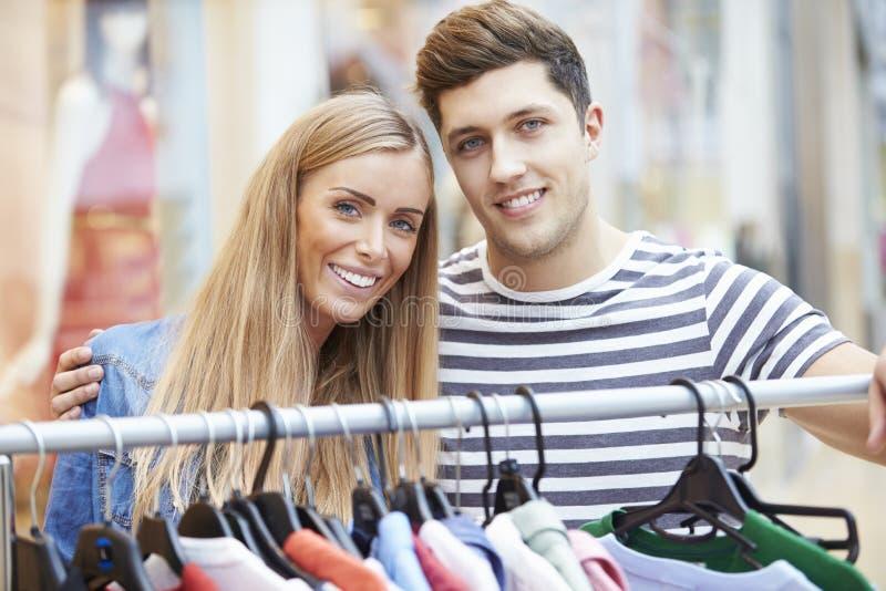 Par som ser kläder på stången i shoppinggalleria arkivbild