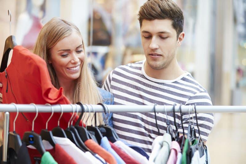 Par som ser kläder på stången i shoppinggalleria royaltyfria foton