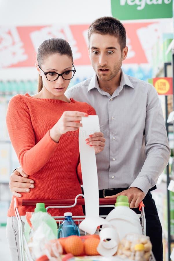 Par som shoppar och kontrollerar ett kvitto royaltyfria foton