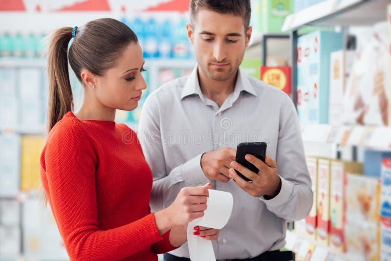 Par som shoppar och kontrollerar ett kvitto arkivfoton