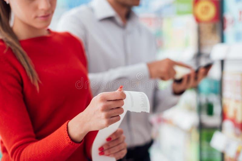 Par som shoppar och kontrollerar ett kvitto arkivbild