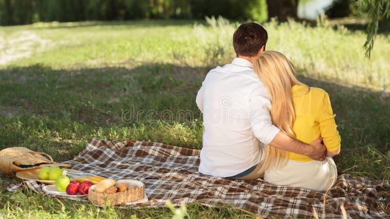 Par som sitter i sommar, parkerar och att ha picknicken på filten royaltyfria foton