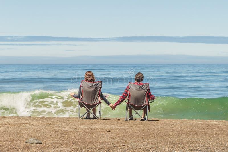 Par som sitter i vikningstolar på stranden royaltyfria bilder