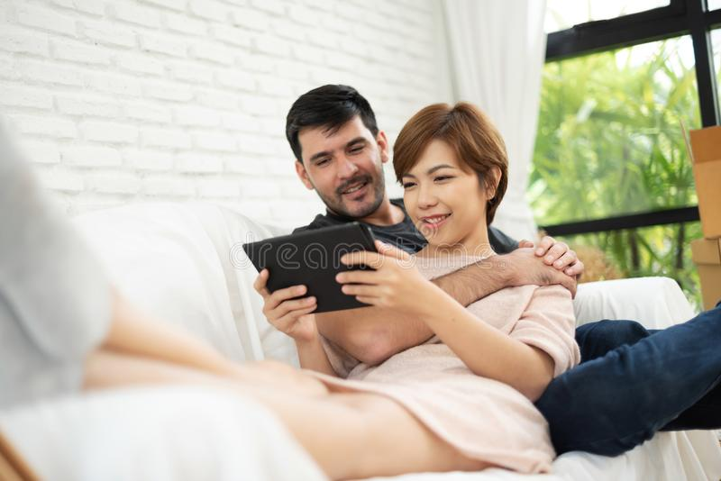 Par som sitter och använder den digitala minnestavlan arkivfoton