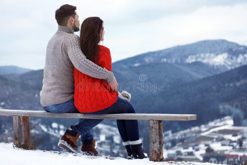 Par som sitter på bänk och tycker om berglandskapet, utrymme för text arkivfoto