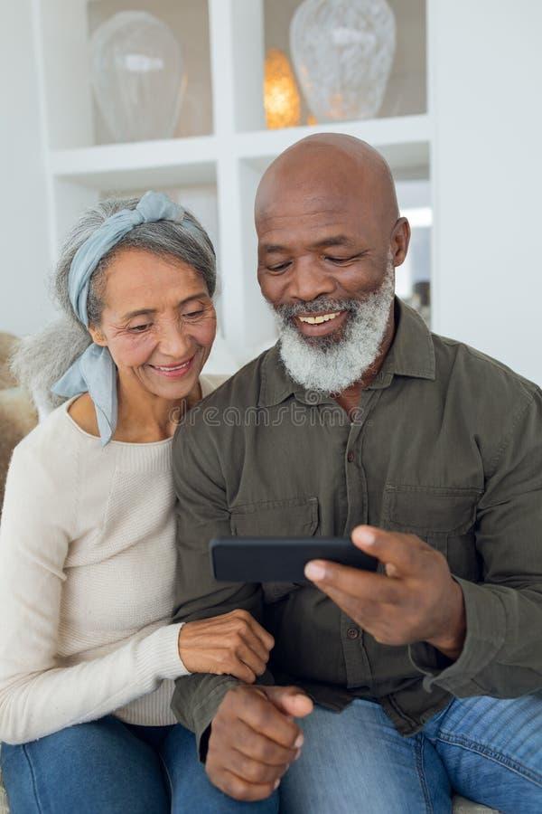 Par som sitter på en soffa inom ett rum, medan se smartphonen royaltyfri bild