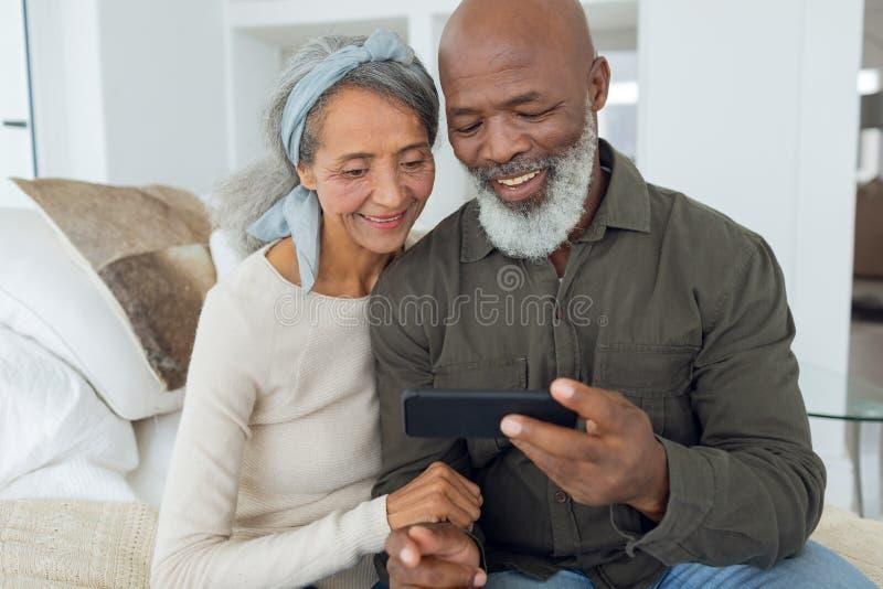 Par som sitter på en soffa inom ett rum, medan se smartphonen royaltyfria foton