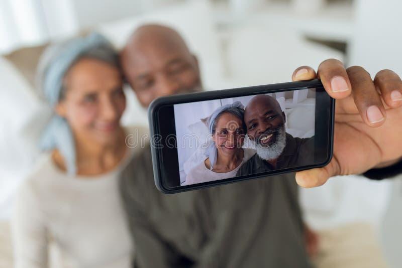 Par som sitter på en soffa inom ett rum, medan ta en bild arkivbild