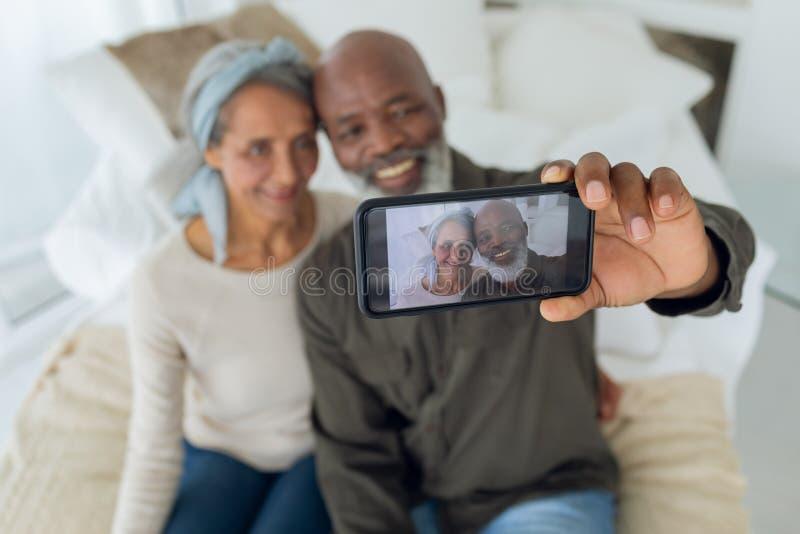 Par som sitter på en soffa inom ett rum, medan ta bilden med smartphonen fotografering för bildbyråer