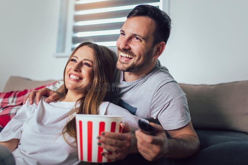 Par som sitter på en vardagsrumsoffa, hållande ögonen på TV och äter popcorn arkivfoton