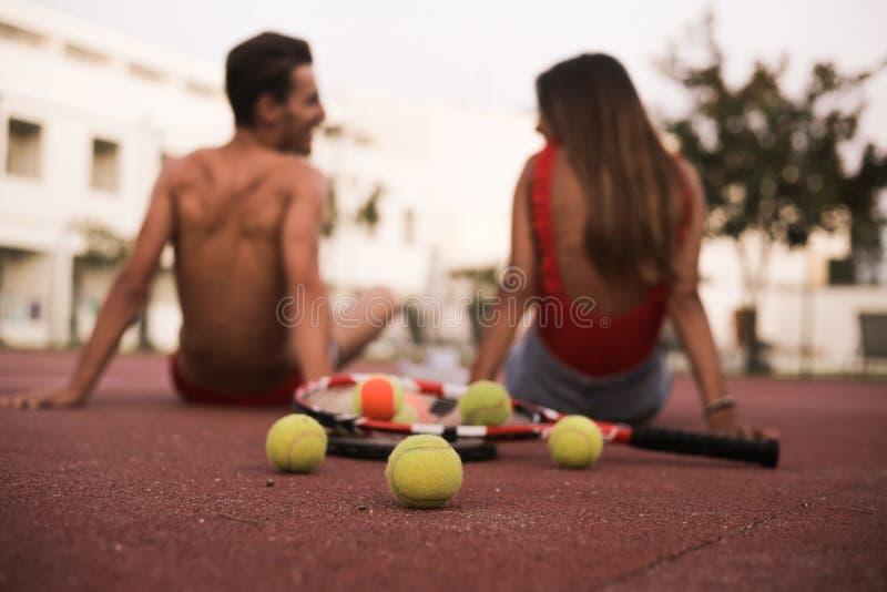 Par som sitter på golvet, når att ha spelat tennis royaltyfri foto