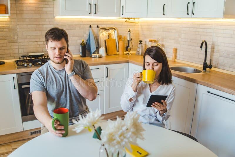 Par som sitter på köket i morgonen som dricker teläsningnyheterna royaltyfria bilder