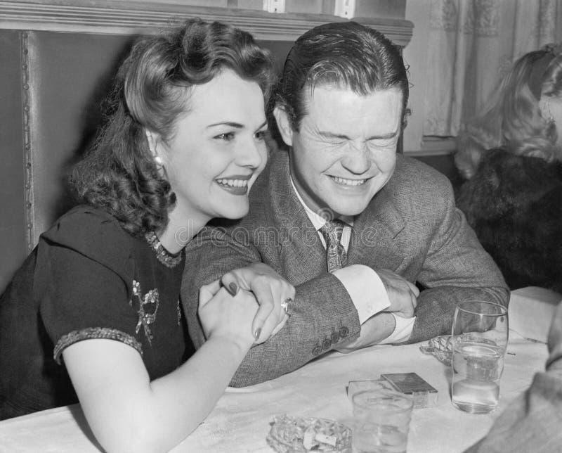 Par som sitter tillsammans att skratta, och lyckligt (alla visade personer inte är längre uppehälle, och inget gods finns Leveran royaltyfri fotografi