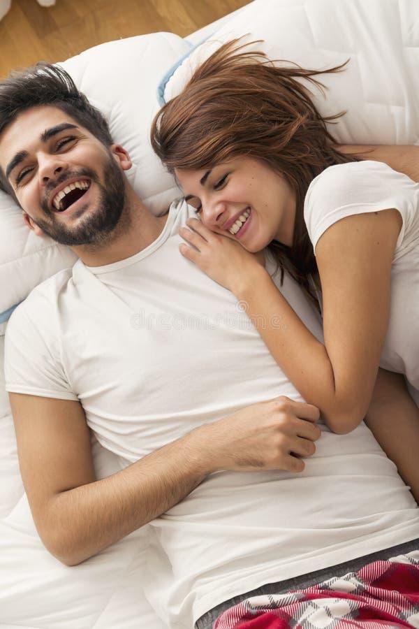 Par som skrattar i säng, når att ha vaknat upp royaltyfri foto