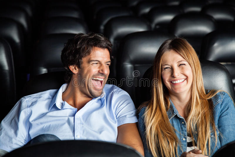 Par som skrattar, medan hålla ögonen på filmen i teater royaltyfri fotografi
