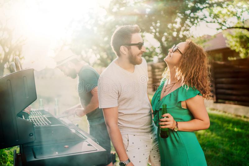 Par som skrattar på bbq-partiet som tycker om drinkar och har en bra tid Utomhus- trädgårdmatlagning royaltyfria foton
