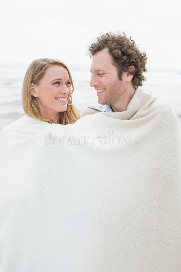 Par som slås in i filt på stranden royaltyfri fotografi