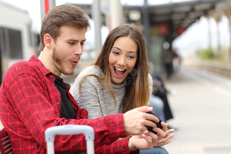 Par som spelar lekar med en smart telefon i en drevstation arkivbilder
