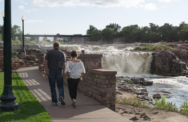 Par som strosar vid Sioux Falls på den stora Sioux River i South Dakota royaltyfri foto