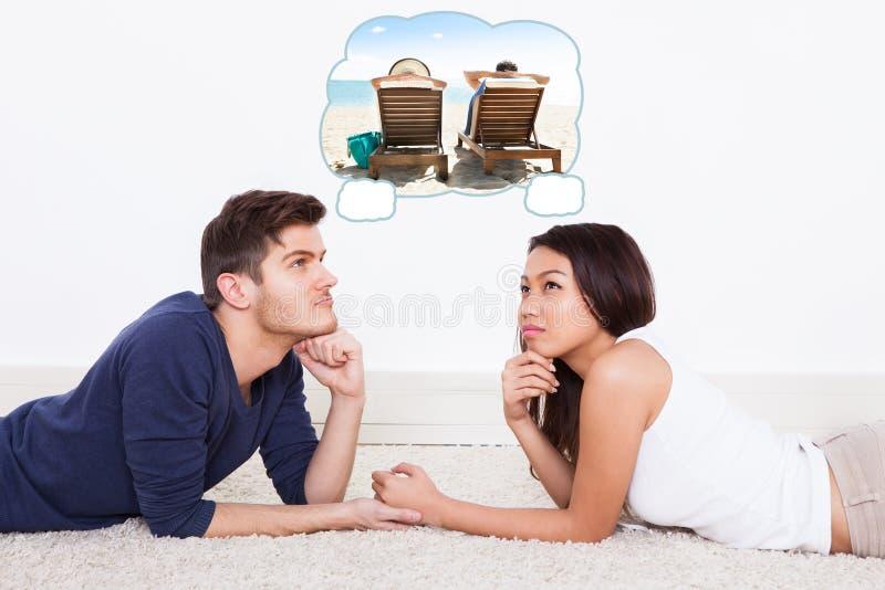 Par som tänker av utgiftersemester på stranden royaltyfri fotografi
