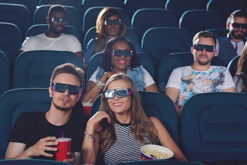 Par som talar i bio och hållande ögonen på film arkivfoto