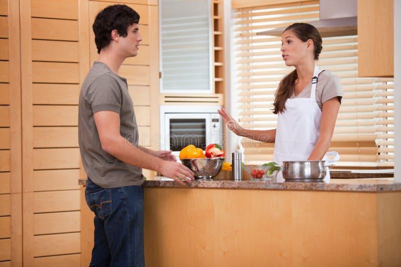 Par som talar i kök royaltyfria bilder