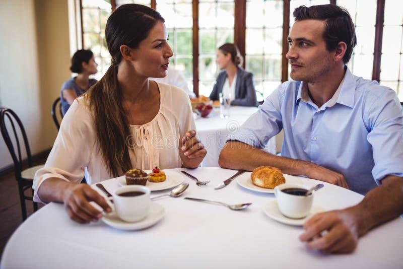 Par som talar med de i restaurang royaltyfria foton