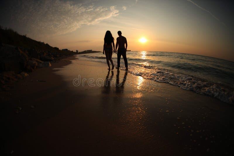 Par som tar ett gåinnehav händer på stranden royaltyfria bilder