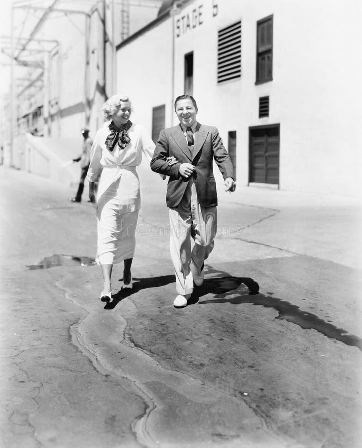 Par som tillsammans går och skrattar (alla visade personer inte är längre uppehälle, och inget gods finns Leverantörgarantier som royaltyfri bild