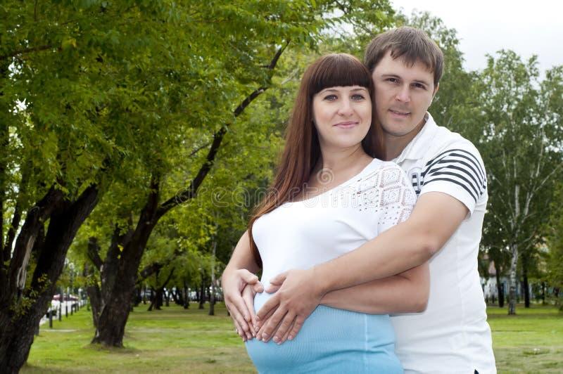 par som tillsammans kramar den gravida kvinnan för lays royaltyfri bild