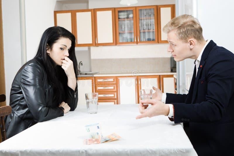 Par som tillsammans löser finanskris på tabellen i kök - peka upphittaren till pengar på tabellen arkivfoto