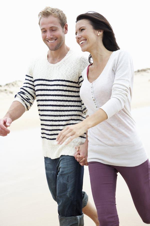 Par som tillsammans promenerar stranden royaltyfri fotografi