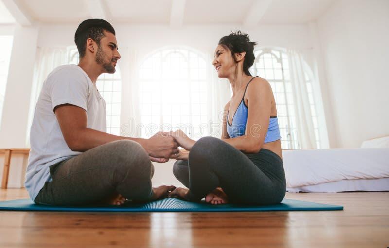 Par som tillsammans sitter på de matta innehavhänderna för yoga arkivbilder