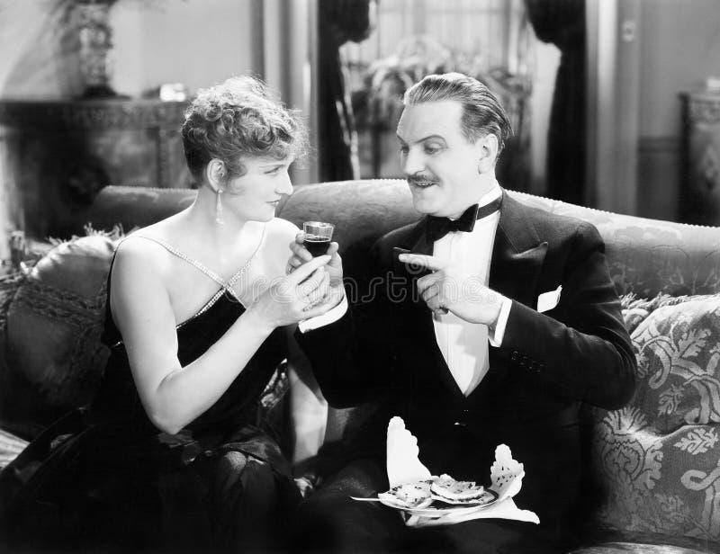 Par som tillsammans sitter på en soffa och har en drink (alla visade personer inte är längre uppehälle, och inget gods finns Leve royaltyfria bilder