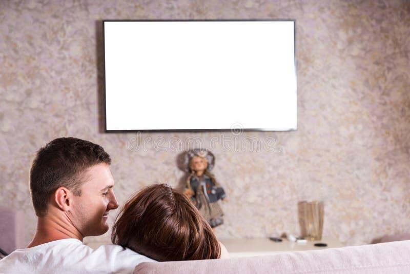 Par som tillsammans smyga sig på soffan och hållande ögonen på TV royaltyfria foton