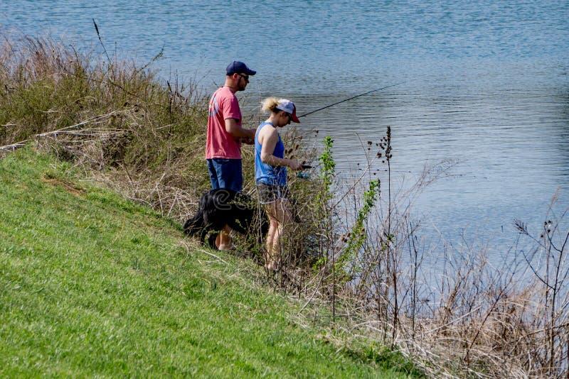Par som tycker om att fiska på Greenfield sjön, Virginia, USA royaltyfri fotografi